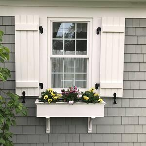 White closed Board and Batten shutters on gray home