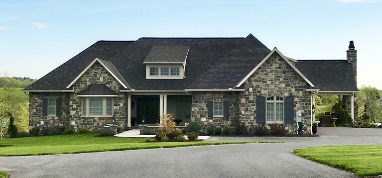 custom home with stone exterior and custom panel exterior shutters