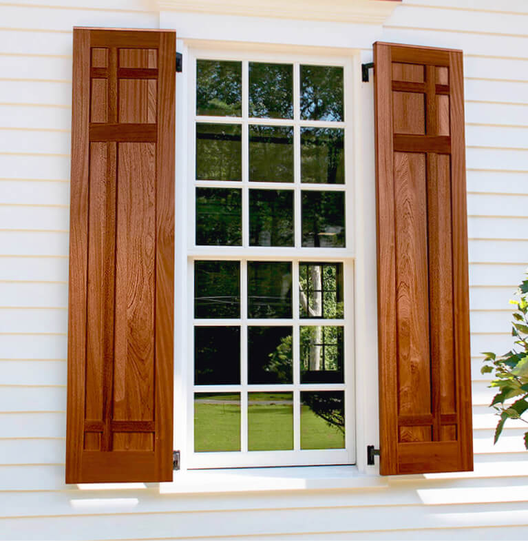 home with white siding and wooden mission style exterior shutters with functional shutter hardware