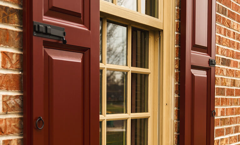 red brick home with red painted wooden panel shutters with shutter locks and shutter pull rings