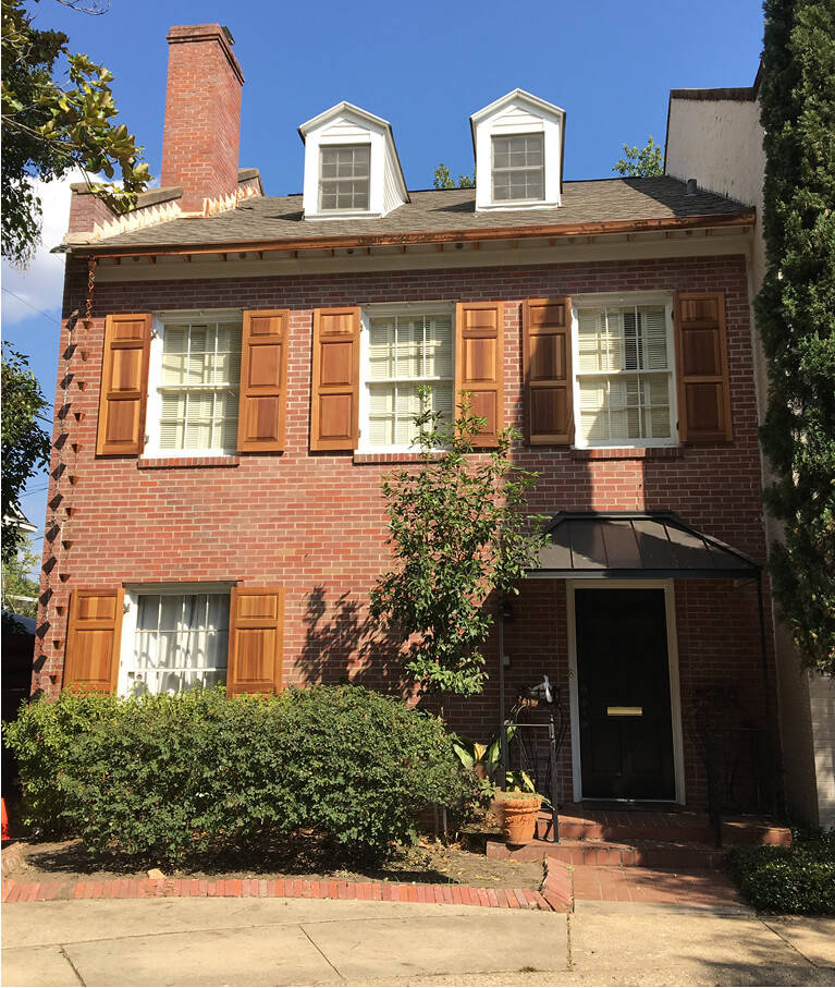 red brick home with unfinished wooden panel shutters