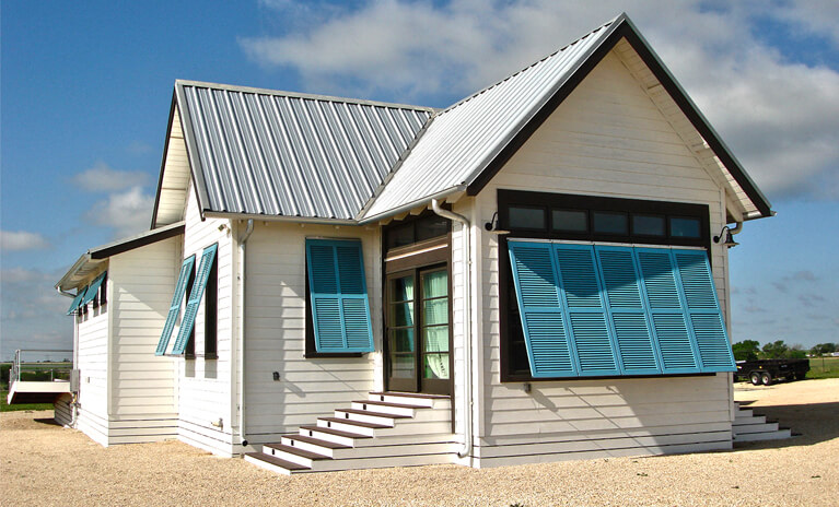 blue topaz hurricane rated bahama shutters on white beach bungalow home