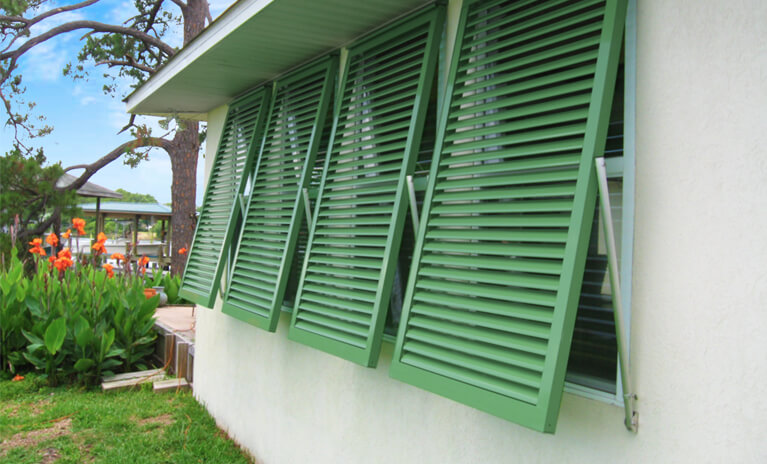 white coastal home with green hurricane rated bahama shutters and functional hardware