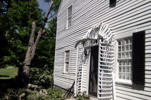 photo of home after tree fell on house damaging shutters