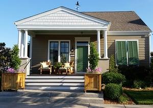 Green bermuda shutters on tan home