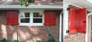 Red bi-fold vertical groove panel shutter on brick home