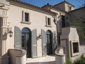 Mediterranean style stucco home with gray arched louver shutters