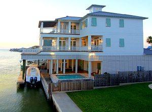 Teal bermuda shutters on white beach house