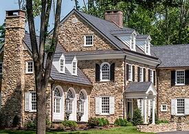 white panel and black louver shutters on tan stone home