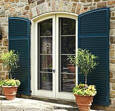 Blue fixed louver shutters with arch tops on tan stone home