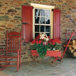 rED PANEL SHUTTERS ON TAN STONE HOME