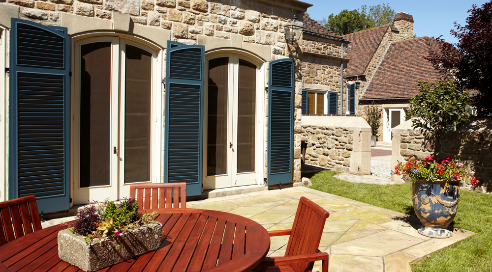 blue Endurian fixed louver shutters with arch tops on sides of doors