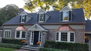 A stone Cape Cod style home with raised panel shutters on its dormer windows.