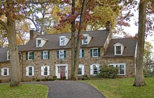 Stone colonial house with white panel shutters on the first floor and green louver shutters on the second floor