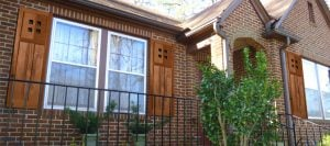 stained wood mission style shutters on brick home
