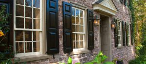 black panel shutters on stone home