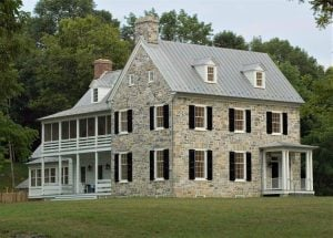 stone colonial farmhouse with panel shutters and louver shutters