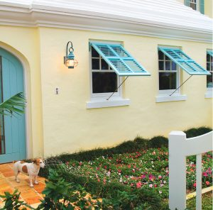 The turquiose shade of these Bermuda shutters was custom matched to make this warm façade come alive with pops of cool color. Bermuda shutters are perfect for shade, breeze, and privacy.
