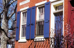 These vibrant blue recessed panel shutters brighten up the brick façade of this historic townhome.