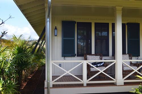blue exterior shutters installed on beach cottage bungalow, both louver and Bermuda
