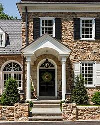 Black louver shutters and white panel shutters on tan stone home