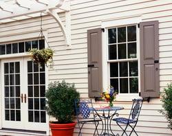 gray panel shutters on white vinyl siding home