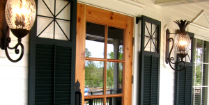 Black louver shutters with custom cutouts on classic white home
