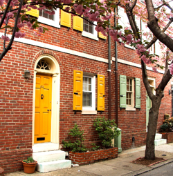 yellow and green panel shutters on brick home
