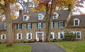 A combination of Timberlane's panel and louver shutters in both green and white on a stone colonial.