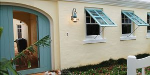 Blue bermuda shutters on tan stucco tropical home