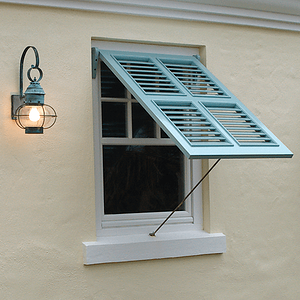 Light blue bermuda shutter on white stucco beach home