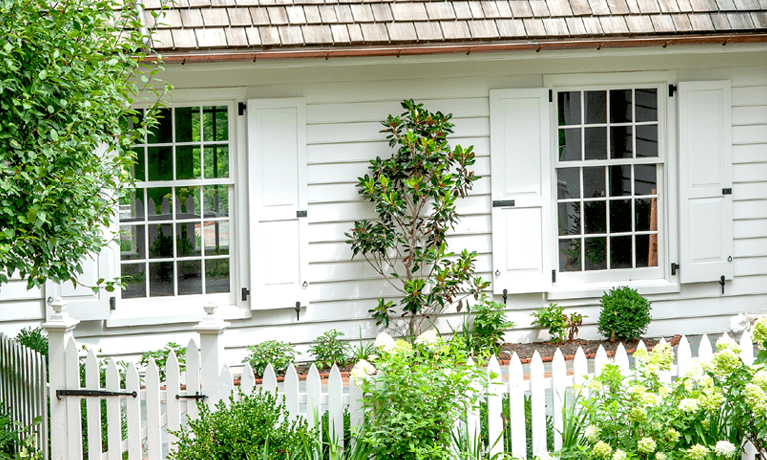 white siding home with functional panel exterior shutters and hardware