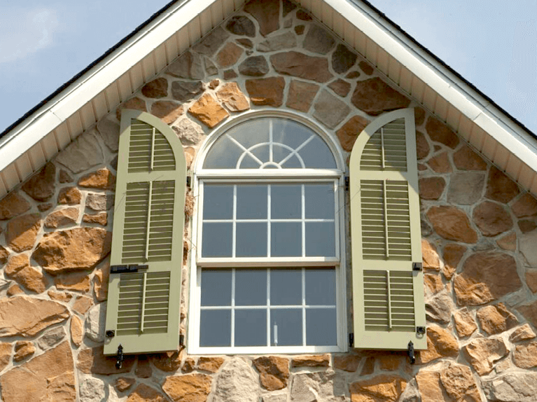 arch top exterior shutters for a stone home
