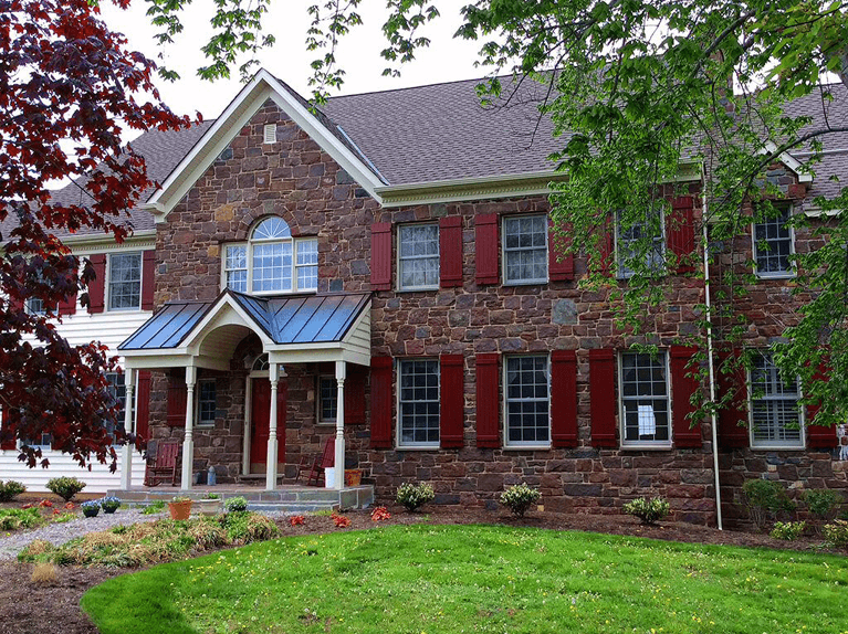 red board and batten exterior shutters for a stone home