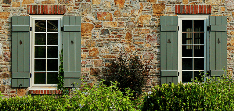 how exterior shutters give a stone home a rustic look