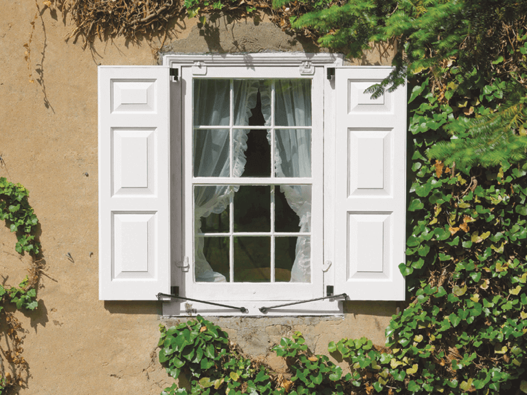 custom shutters with functional hardware to enhance the exterior of a stucco home