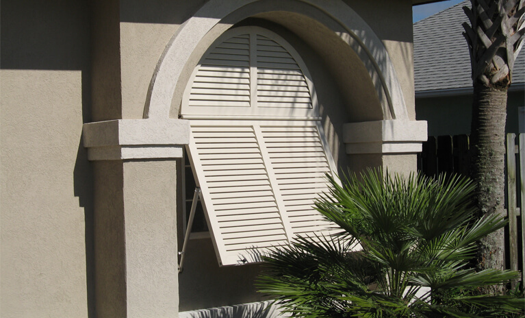 tan home with custom bahama style shutters with tilt rods to control light and airflow