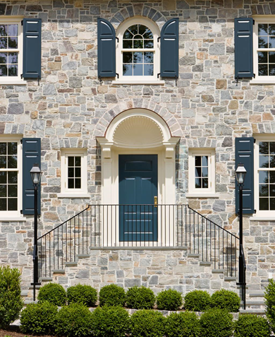 blue panel shutters on gray and tan stone home