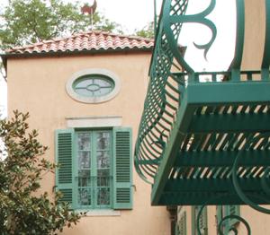 green louver shutters on peach stucco home