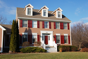 red panel shutters on tan brick home